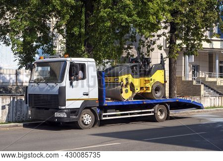A Tow Truck Transports The Road Roller On A Stationary Platform To The Place Of Work. Background For