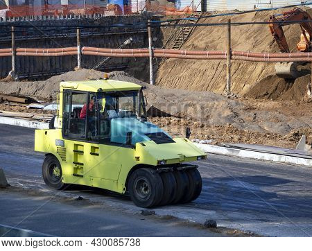 The Road Roller Compacts The Asphalt Surface On The Road. Road Roller At A Construction Site Against
