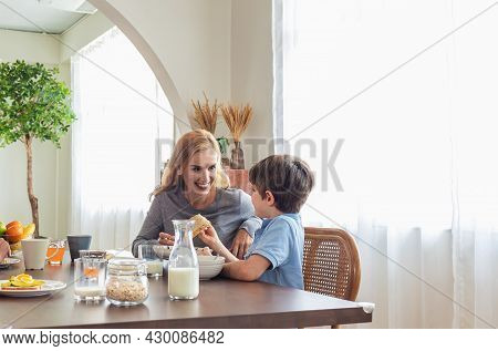 Happy Caucasian Family Eat Breakfast Together At Home. Mother And Children Enjoying Meal At The Kitc