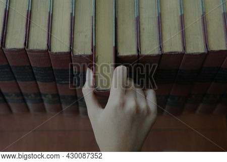 Jakarta, Indonesia-august 16, 2021: Close Up Of A Hand Taking An Encyclopedia Book From A Bookshelf