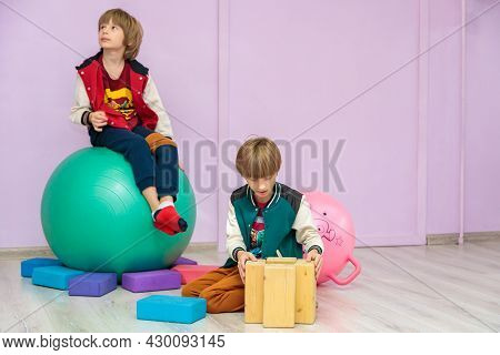 Two Boys In The Hall Collect Cubes, One Sits On A Ball. Boys Study In A Circle.