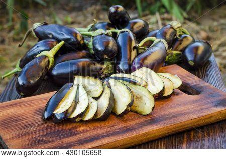 Sliced Slices Along Fresh Eggplants On Wooden Kitchen Board