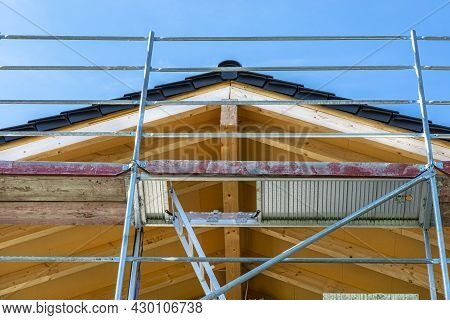 The Roof Truss Seen From Below With Chipboards Nailed In, Visible Metal Scaffolding.