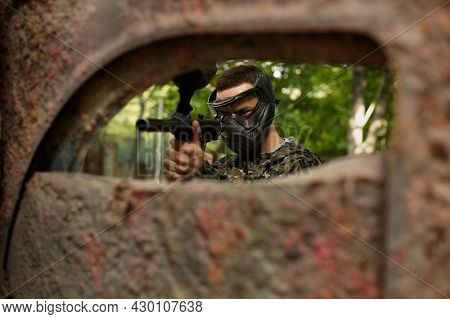 Paintball player in uniform and mask in forest