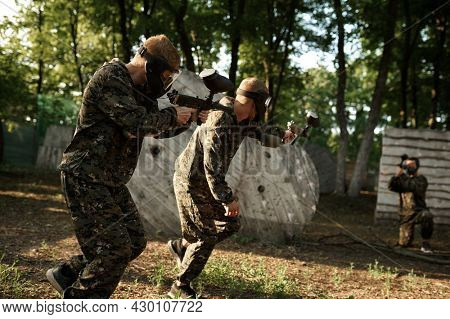 Team in uniform playing paintball in the forest