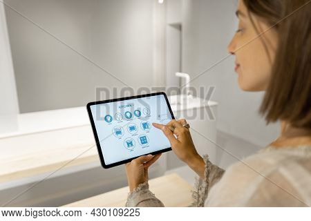 Young Woman Controls Smart Kitchen Appliances With A Digital Tablet While Standing At Modern Kitchen