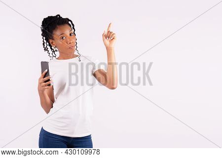 Afro American Woman Pointing Upwards And Looking Sternly At The Camera
