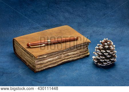 antique leather-bound journal with decked edge handmade paper pages with a stylish pen and a decorative pine cone against blue handmade paper, journaling or winter holiday greetings concept