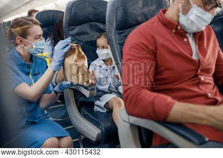 Girl In Protective Face Mask Looking At Female Flight Attendant Serving Lunch To Little Passenger