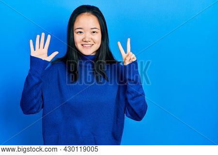 Young chinese girl wearing casual clothes showing and pointing up with fingers number seven while smiling confident and happy.
