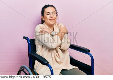 Young hispanic woman sitting on wheelchair hugging oneself happy and positive, smiling confident. self love and self care