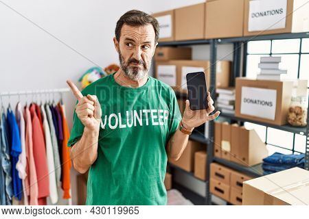 Middle age man with beard wearing volunteer t shirt holding smartphone pointing aside worried and nervous with forefinger, concerned and surprised expression