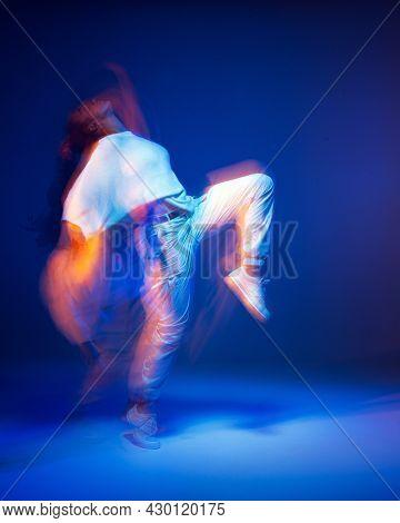 Dancing Girl In White Sportswear In Neon Studio Light. Female Dancer Show Expressive Hip Hop Dance.