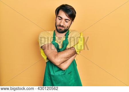 Young hispanic man wearing cleaner apron and gloves hugging oneself happy and positive, smiling confident. self love and self care