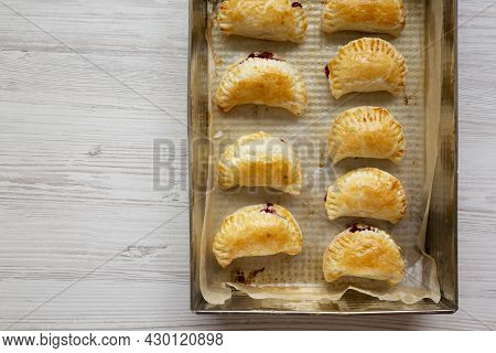 Homemade Cherry Hand Pies In A Baking Pan, Top View. Flat Lay, Overhead, From Above. Copy Space.
