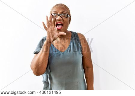 Mature hispanic woman wearing glasses standing over isolated background shouting and screaming loud to side with hand on mouth. communication concept.