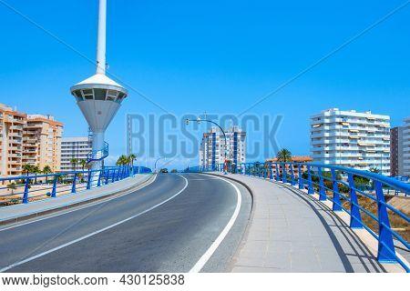 LA MANGA, SPAIN - JULY 29, 2021: View of the Estacio movable bridge over the Gola del Puerto canal, in La Manga del Mar Menor, Murcia, Spain, connecting the Mar Menor lagoon and the Mediterranean sea