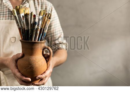 Male artist holding clay jug with paintbrush. Man artist painter and paint brush in creative studio as art concept