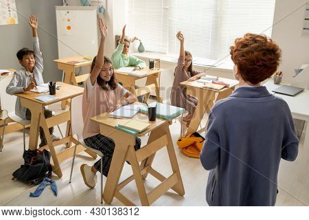 Young teacher standing in front of intercultural schoolkids raising hands at lesson
