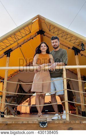 Amorous couple enjoying their honeymoon by glamping house at summer resort