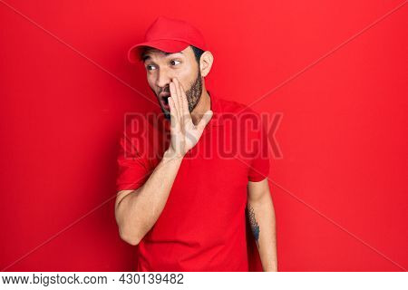 Hispanic man with beard wearing delivery uniform and cap hand on mouth telling secret rumor, whispering malicious talk conversation