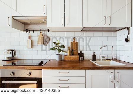 Kitchen Brass Utensils, Chef Accessories. Hanging Kitchen With White Tiles Wall And Wood Tabletop.gr