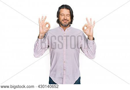 Middle age handsome man wearing business shirt relax and smiling with eyes closed doing meditation gesture with fingers. yoga concept.