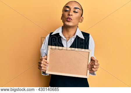 Hispanic man wearing make up and long hair holding empty corkboard looking at the camera blowing a kiss being lovely and sexy. love expression.