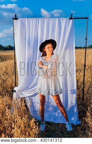 Young Beautiful Woman Dressed In A White Polka-dot Dress And Black Hat Standing At Golden Oat Field