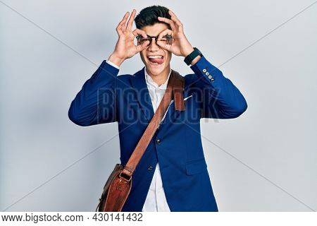 Young hispanic man wearing business clothes doing ok gesture like binoculars sticking tongue out, eyes looking through fingers. crazy expression.