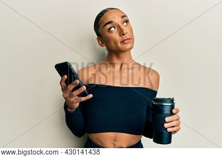 Hispanic transgender man wearing make up and long hair using smartphone and drinking a cup of coffee smiling looking to the side and staring away thinking.