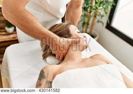 Young caucasian woman at physiotherapy clinic getting muscle massage by professional therapist. Physiotherapist man doing cervical treatment to client