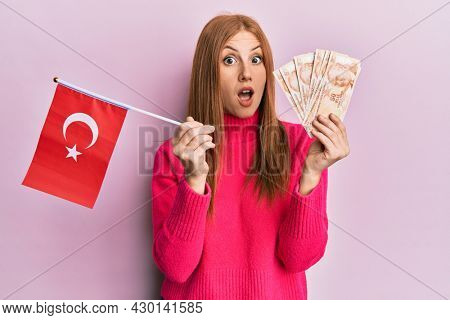 Young irish woman holding turkey flag and liras banknotes afraid and shocked with surprise and amazed expression, fear and excited face.