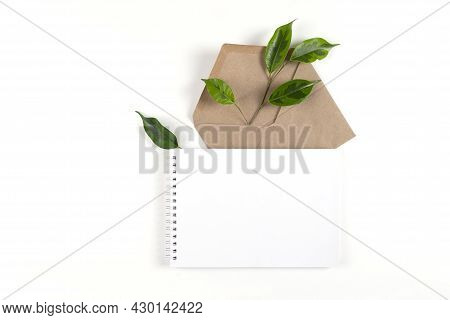 Notepad And An Envelope Made From Recycled Paper Lie On White Surface With Sprig Of A Green Plant. E