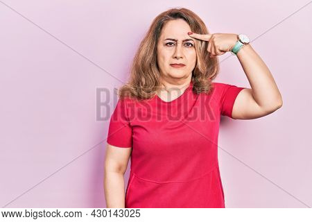 Middle age caucasian woman wearing casual clothes pointing unhappy to pimple on forehead, ugly infection of blackhead. acne and skin problem