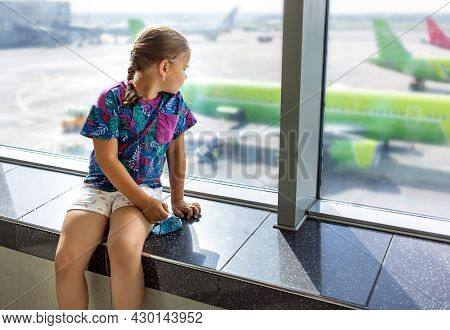 Child At The Airport Near The Window Is Looking At Airplanes And Waiting For Time Of Flight. She Is