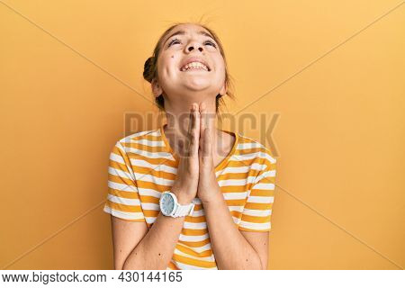 Beautiful brunette little girl wearing casual striped t shirt begging and praying with hands together with hope expression on face very emotional and worried. begging.