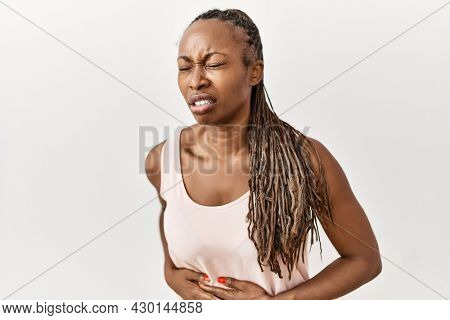 Black woman with braids standing over isolated background with hand on stomach because indigestion, painful illness feeling unwell. ache concept.