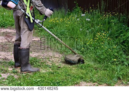 Man In Special Protective Clothing With Lawn Mower In His Hands Mows Grass. Gardener Mows Grass With