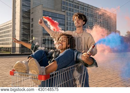 Girl in shopping cart and her boyfriend having fun with firecrackers in the street
