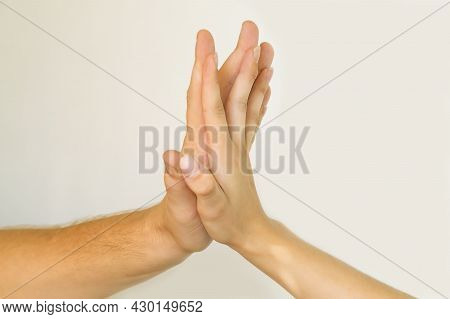 The Hands Of A Guy And A Young Girl Gently Touch. A Happy Couple In Love Holding Hands. Close-up Of