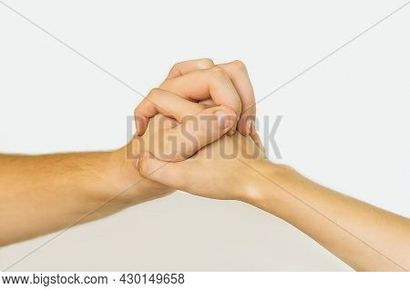 A Young Couple In Love Holding Hands. Close-up Of A Woman And A Man Shaking Hands On A Light Backgro