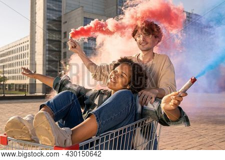 Happy multiracial teenage couple with firecrackers having fun against modern architecture