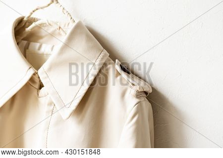 A Beige Trench Coat Isolated Over White And Close Up.