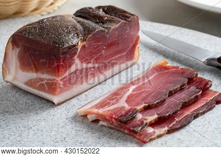 Piece of German Sudtiroler speck and slices on a cutting board close up