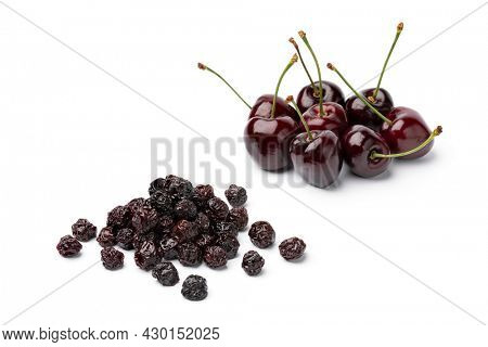 Heap of fresh red ripe juicy cherries and a heap of preserved ones isolated close up on white background