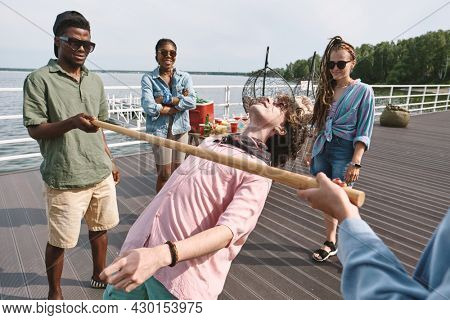 Group of joyful young people playing limbo game on pier by the lake when enjoying small party
