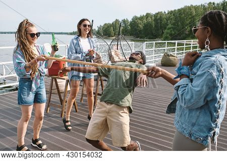 Young man bending backwards to walk under vertical bar in hands of his friend to win limbo game