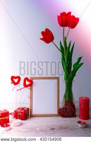 Holiday Mock Up. Tulip Flowers In Glass Vase With Picture Frame Decor On Wooden Table Background Wal