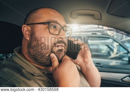 Puzzled Man With Glasses Talking On Phone While Driving Car. Emotion Of Doubt And Distrust On Face O